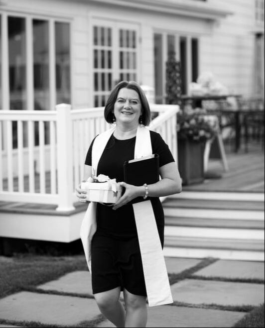 Black and white image of Rev. Sarah walking and holding a box